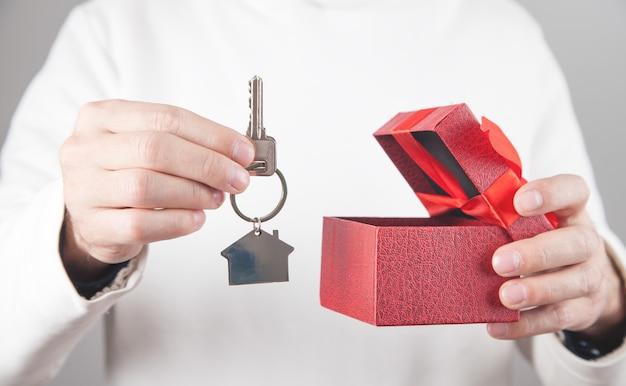 Mężczyzna trzyma dom i klucze z pudełkiem.
