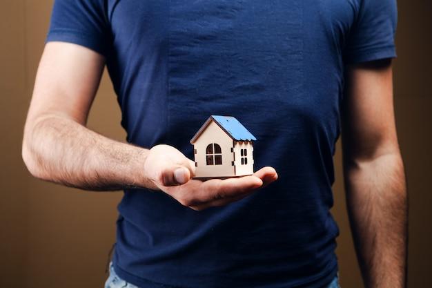 Mężczyzna trzyma dom na brązowym