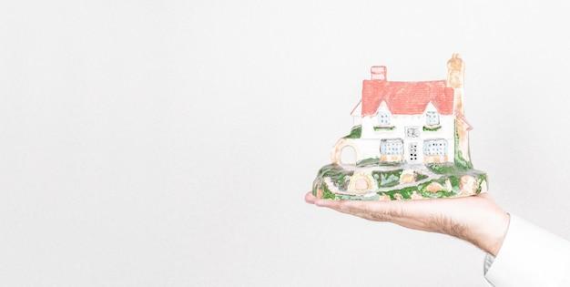 Mężczyzna trzyma dom na szarym tle