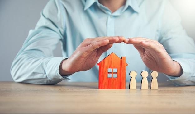 Mężczyzna trzyma drewnianą rodzinę z domu