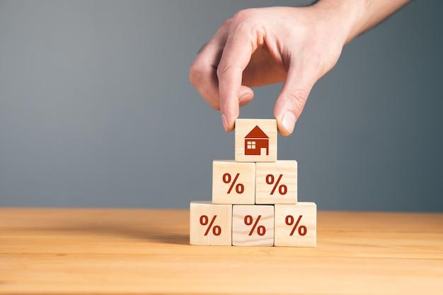 Mężczyzna trzyma drewniane bloki z procentem i domem