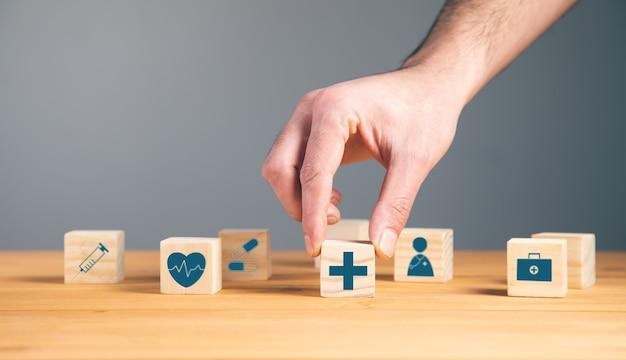 Mężczyzna trzyma drewniane klocki z medycznym symbolem opieki zdrowotnej