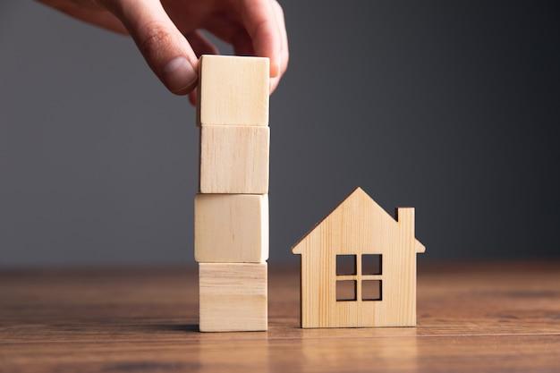 Mężczyzna trzyma drewniane kostki i model domu na stole