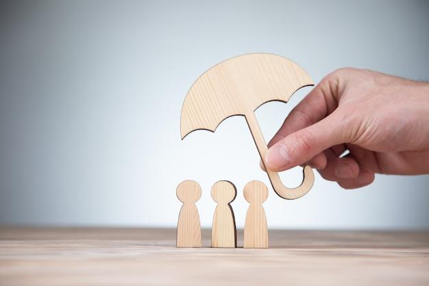 Mężczyzna trzyma drewniane ludzi z parasolem na stole