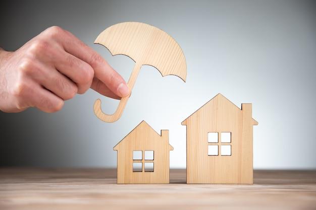 Mężczyzna trzyma drewniane modele domów i parasol