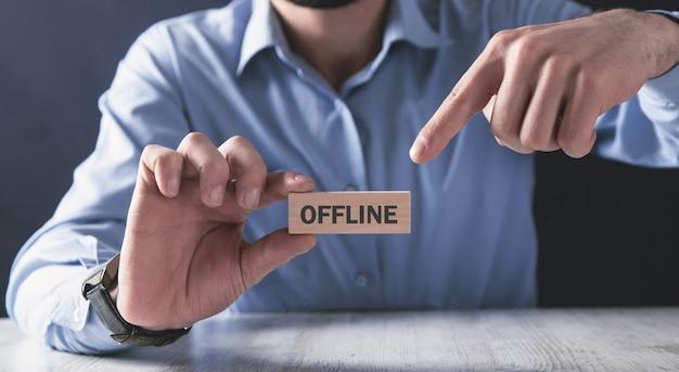 Mężczyzna trzyma drewniany blok. offline