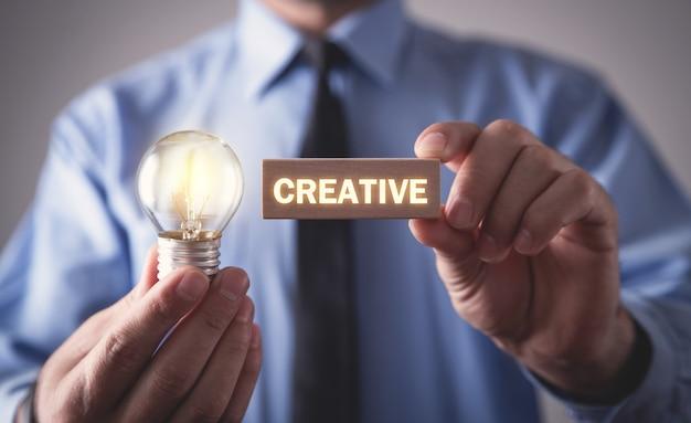 Mężczyzna trzyma drewniany blok ze świecącą żarówką. kreatywny, pomysł, innowacja, technologia