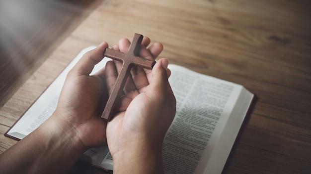 Mężczyzna trzyma drewniany krzyż w rękach na biblii i boskim świetle. pojęcie religii.