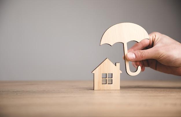 Mężczyzna trzyma drewniany parasol i dom