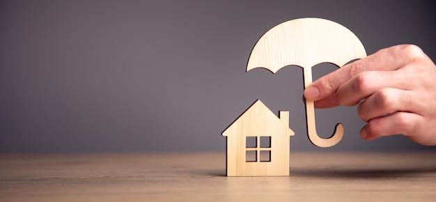 Mężczyzna trzyma drewniany parasol i model domu