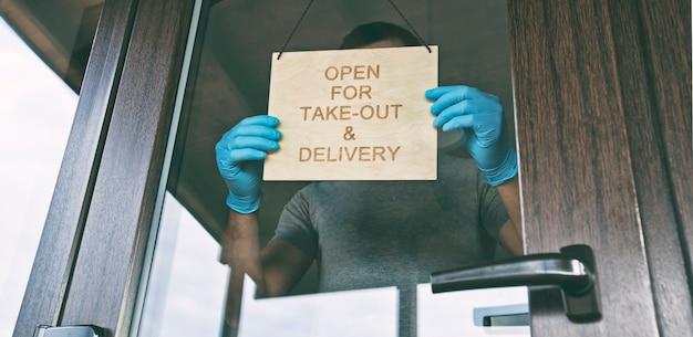 Mężczyzna trzyma drewniany znak z tekstem: otwarte na wynos i dostawę