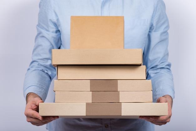 Mężczyzna trzyma dużo kartonów. koncepcja ekspresowej dostawy. dostawa paczek do domu.