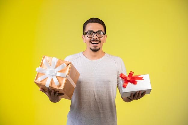 Mężczyzna trzyma dwa pudełka na prezenty i wygląda na szczęśliwego.