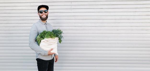 Mężczyzna trzyma eko torbę wypełnioną sklepem spożywczym. warzywa i owoce zwisają z torby. pojęcie ekologii ochrony środowiska.