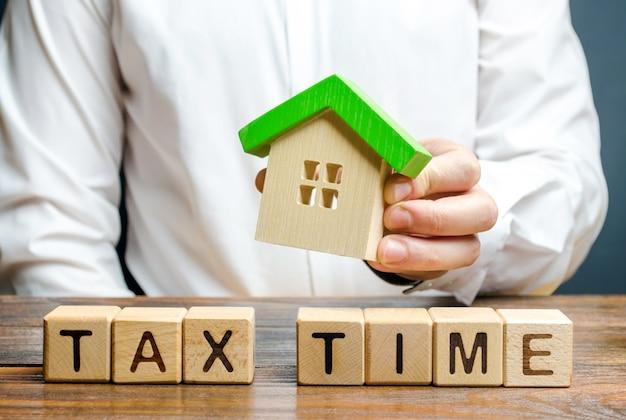 Mężczyzna trzyma figurę domu nad napisem czas podatkowy. opodatkowanie, podatek dochodowy