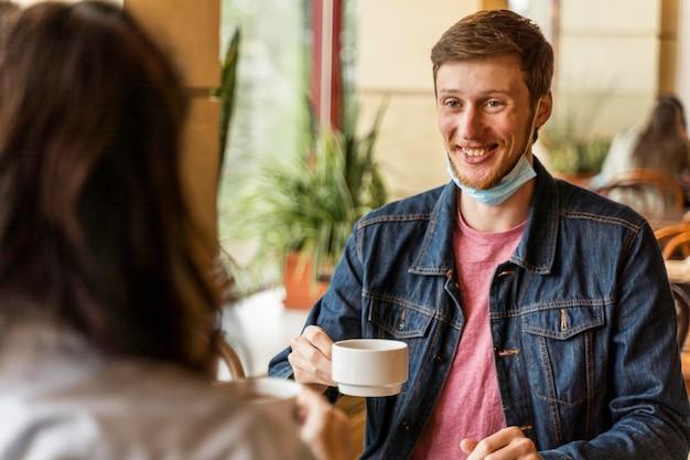 Mężczyzna trzyma filiżankę herbaty ze swoim przyjacielem
