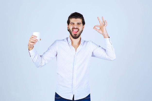 Mężczyzna trzyma filiżankę kawy i cieszył się smakiem