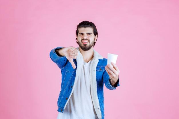 Mężczyzna trzyma filiżankę kawy i nie lubi jej