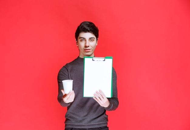 Mężczyzna trzyma filiżankę kawy i pokazuje przepis