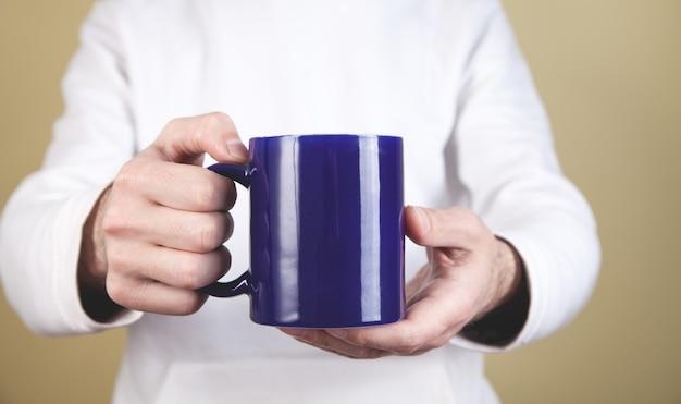 Mężczyzna trzyma filiżankę kawy na żółtym tle.
