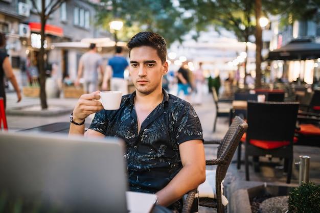 Mężczyzna trzyma filiżankę kawy patrzeje laptopu ekran