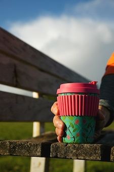 Mężczyzna trzyma filiżankę zrównoważonej bambusowej kawy w parku. zrównoważona koncepcja kawy na wynos. świadoma konsumpcja. ochrona środowiska. recykling.