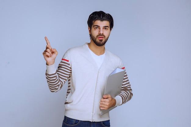 Mężczyzna trzyma folder projektu i wskazuje powyżej.