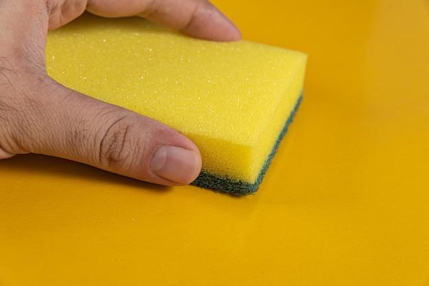Mężczyzna trzyma gąbkę kuchenną na żółtym tle