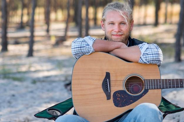 Mężczyzna trzyma gitarę akustyczną