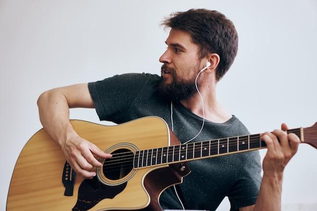Mężczyzna trzyma gitarę wykonując piosenkę z czarną koszulką
