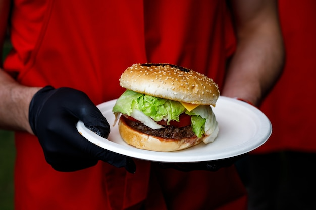 Mężczyzna trzyma gotowy smaczny burger w ręce w czarnych rękawiczkach.