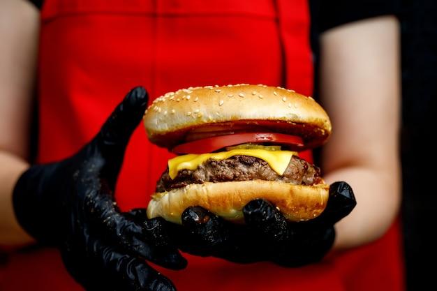 Mężczyzna trzyma gotowy smaczny burger w rękach w czarnych rękawiczkach.