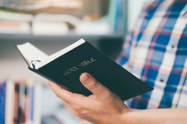 Mężczyzna trzyma i czyta świętą chrześcijańską biblię