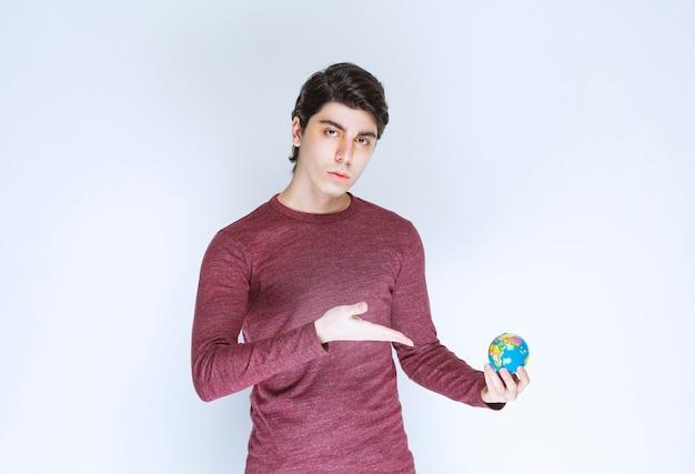 Mężczyzna trzyma i demonstruje mini kulę ziemską.