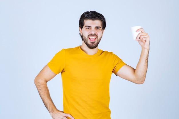 Mężczyzna trzyma i promuje filiżankę kawy.