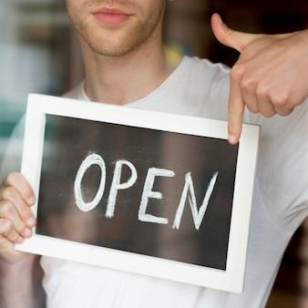 Mężczyzna trzyma i wskazuje przy otwartym sklep z kawą znakiem