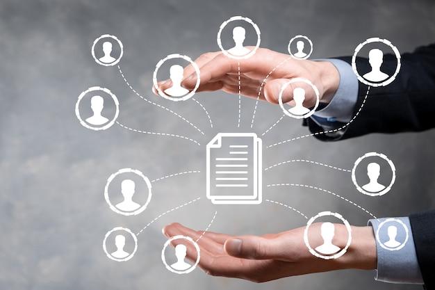 Mężczyzna trzyma ikonę dokumentu i użytkownika. korporacyjny system zarządzania danymi dms i zarządzanie dokumentami