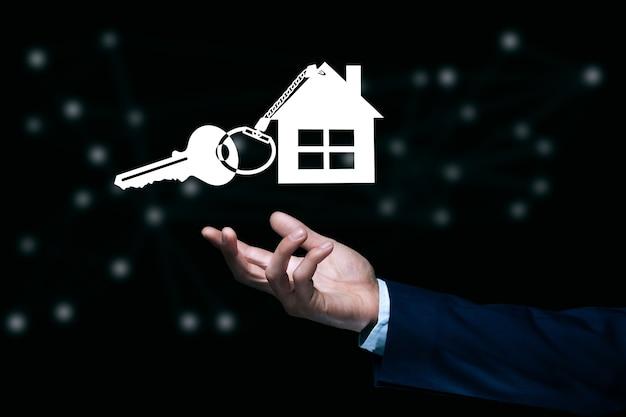 Mężczyzna trzyma ikonę klucza domu na ciemnym tle