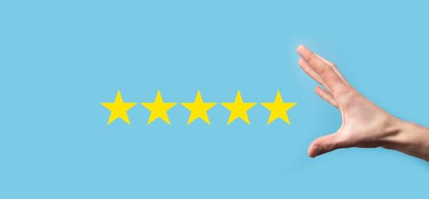 Mężczyzna trzyma inteligentny telefon w rękach i daje pozytywną ocenę, ikona pięciogwiazdkowy symbol, aby zwiększyć ocenę koncepcji firmy na niebieskim tle. doświadczenie obsługi klienta i badanie satysfakcji biznesowej.