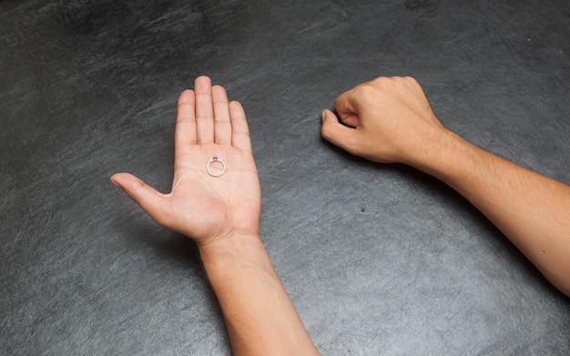 Mężczyzna trzyma jedną rękę zamkniętą, a drugą otwartą, zgadywanie ręki