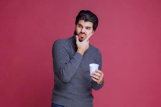 Mężczyzna trzyma jednorazową filiżankę kawy i myśli.