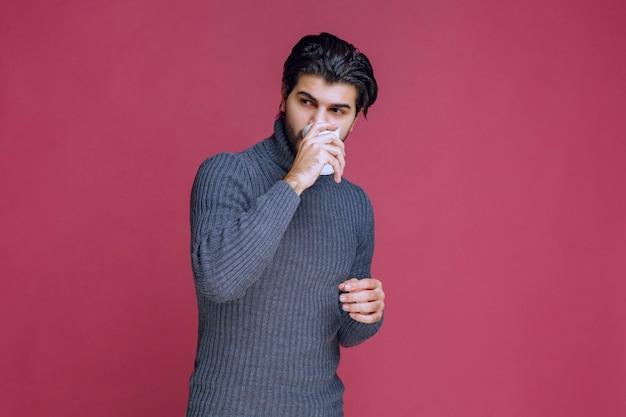 Mężczyzna trzyma jednorazową filiżankę kawy i pije ją.
