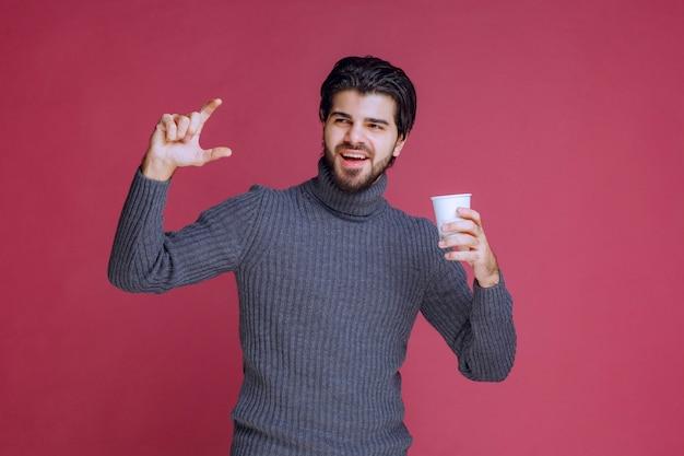 Mężczyzna trzyma jednorazową filiżankę kawy i pokazuje, ile potrzebuje.