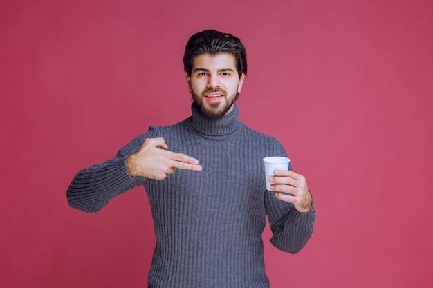Mężczyzna trzyma jednorazową filiżankę kawy i wskazuje na nią.