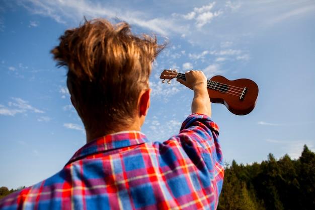 Mężczyzna trzyma jego gitarę ukulele w powietrzu