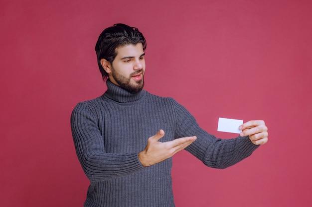 Mężczyzna trzyma jego wizytówkę i wskazuje na to.