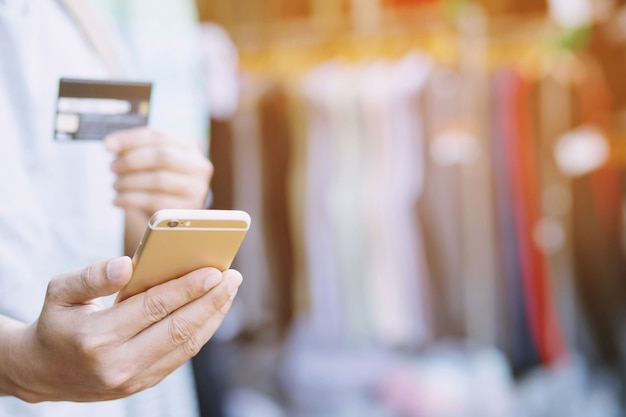 Mężczyzna trzyma kartę cradit i korzysta ze smartfona