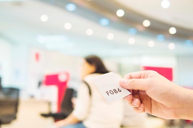 Mężczyzna trzyma kartę kolejki podczas oczekiwania w nowoczesnej recepcji