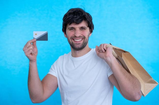Mężczyzna trzyma kartę kredytową i torby na zakupy