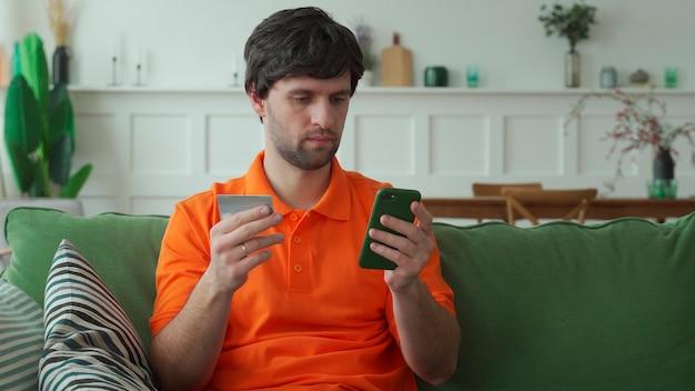 Mężczyzna trzyma kartę kredytową i używa smartfona do zakupów online w domu